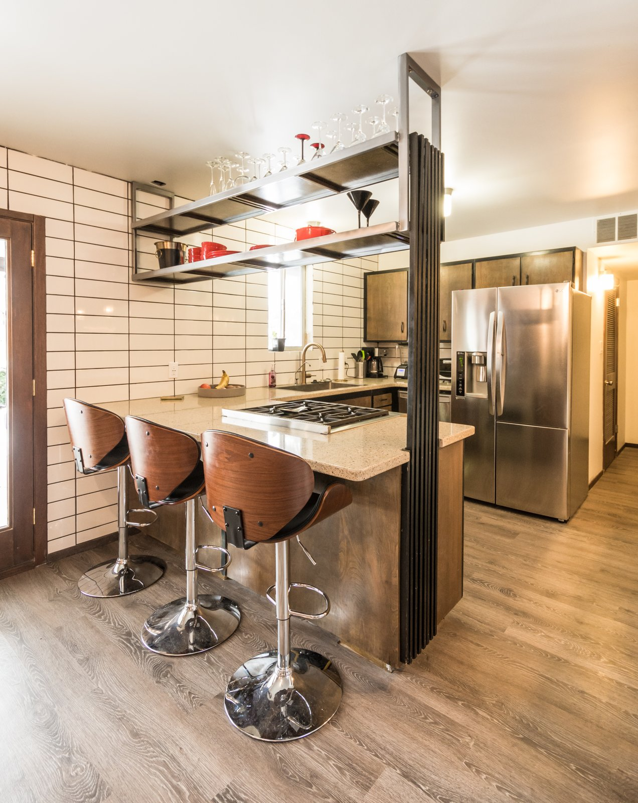 Original kitchen cabinets with new appliances, updates shelf hung from ceiling and full height back splash and original repurposed vertical wood slats  Ron Molen Revival