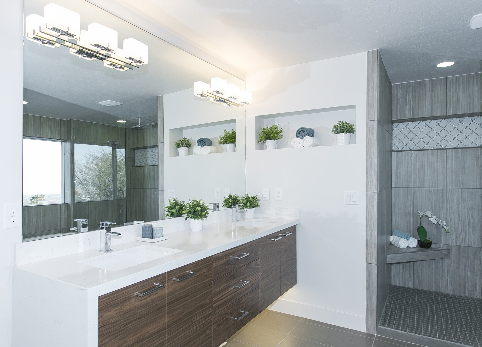 """This master bathroom has been outfitted with a floating vanity, under cabinet lights, back lit mirrors, a glass shower door, soaking tub and of course, a """"throne room"""".  King of the Wasatch"""