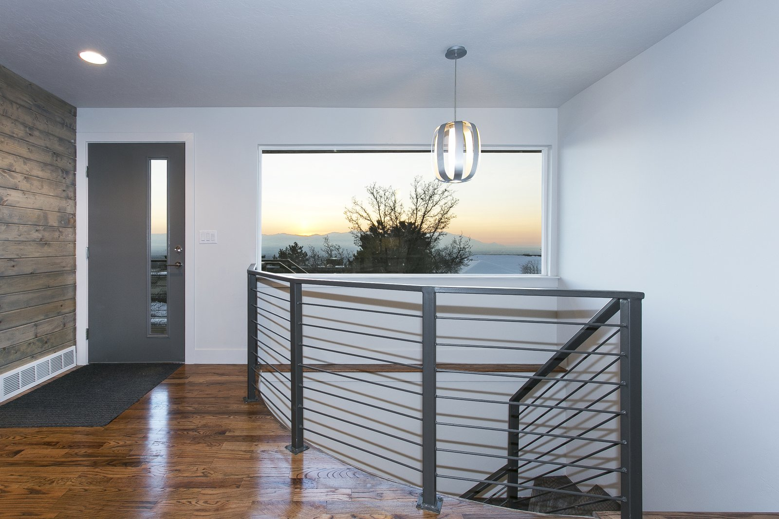 The front entry has a equal blend of oak, cedar and steel railing that creates a great space to soak in the Salt Lake Valley views of the Oquirrh mountain range.  King of the Wasatch