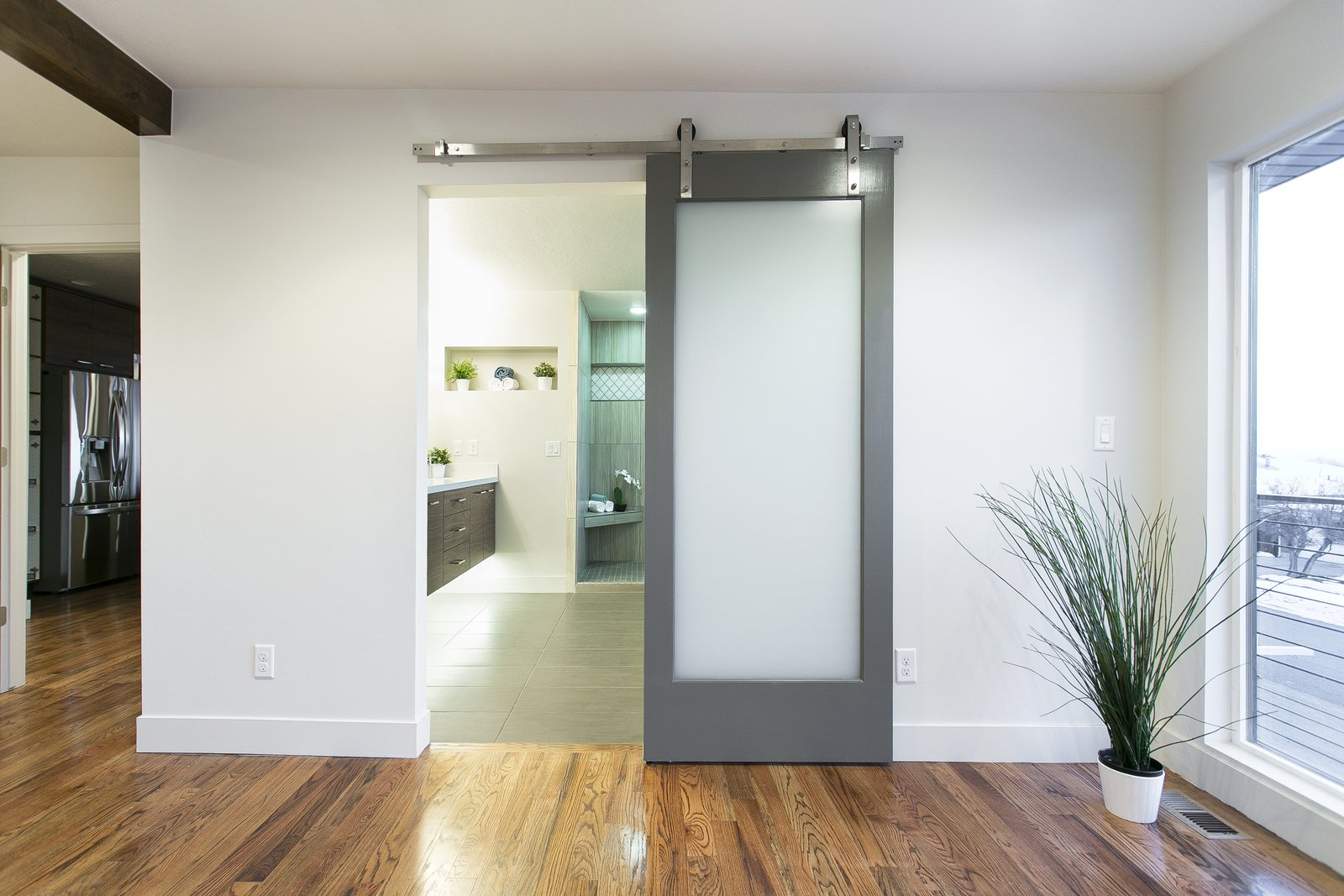 This perfectly placed barn door leads from the master bedroom to the newly renovated modern bathroom with floating cabinets and under cabinet lighting.  King of the Wasatch