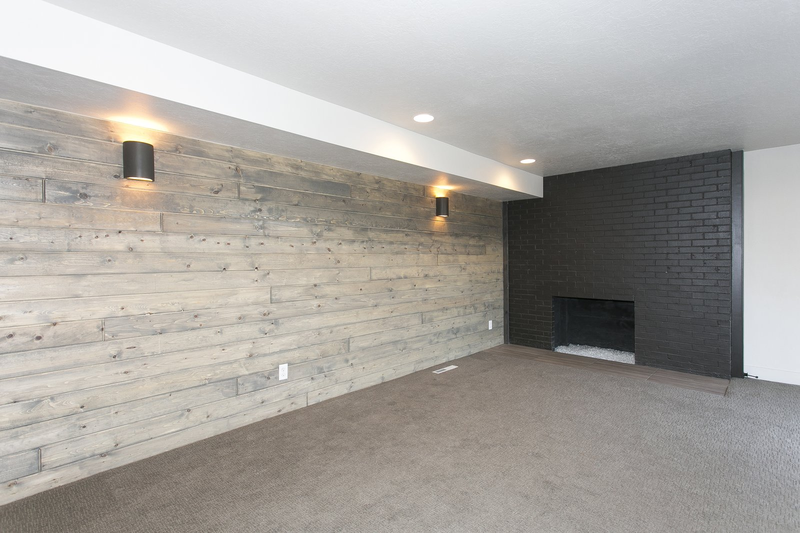 Basement Family room with wood accent wall and painted black brick fireplace.  King of the Wasatch