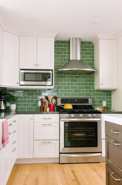 "In this kitchen with white cabinets, Fireclay Tile in a classic subway pattern go beyond the standard 18"" high backsplash, which brings the eye up the walls of the kitchen. The gloss of the tiles allows light to reflect throughout the space, keeping it bright and cheery despite the darker color."