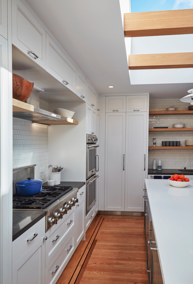 The island separates  a working side, a cleaning side, a social side and a circulation side.  A Danish Inspired Kitchen