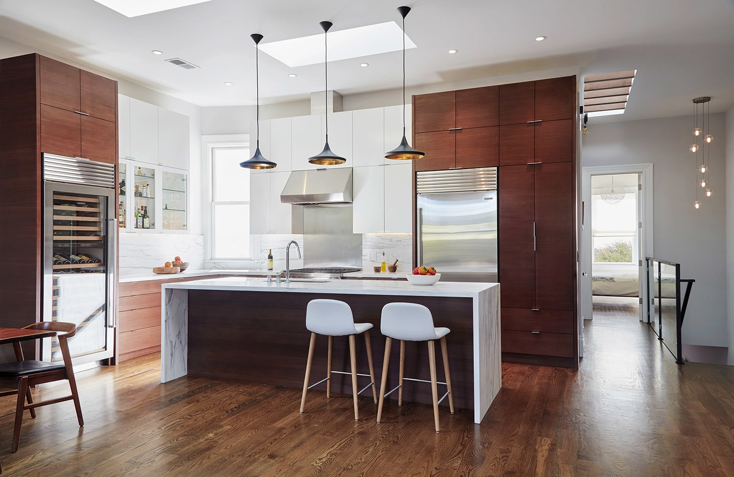 Tall ceiling and tall cabinets anchor this large multi-purpose room.  A Kitchen for the Boys by Benjamin Farrell