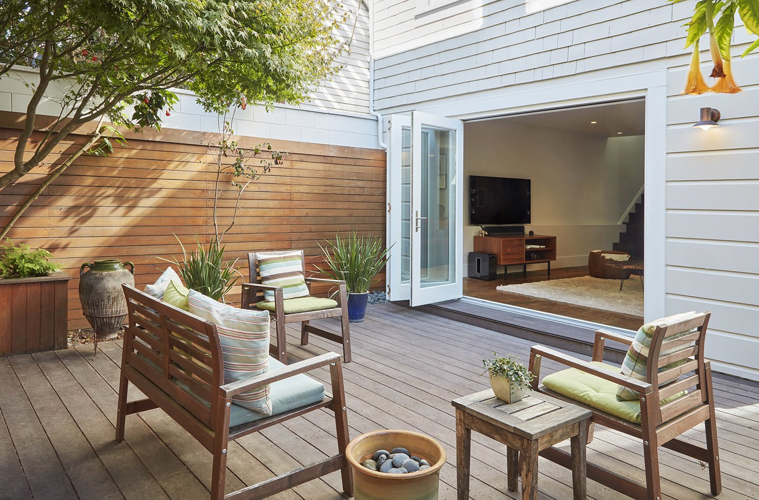 Large folding doors open up a new Garden room to the rear yard deck.  A Kitchen for the Boys by Benjamin Farrell