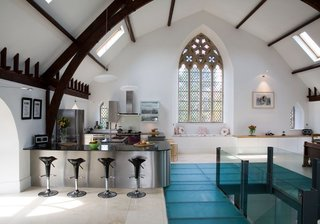 In Kelso, Scotland, a centuries-old stone church was converted into a five-bedroom house where the upper floor of the church is one large, open space that houses a kitchen, dining area, living room, and games space.