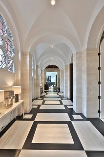 With no interior partitions to divide up the space, the long side aisle of this converted 1910 church in Toronto, Canada maintains the rhythm of the groin vaults, now plastered over and lit with minimalist fixtures.