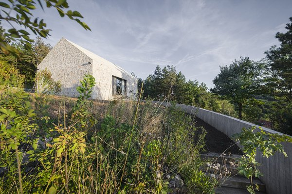 The approach to the home is defined by a concrete wall and a gravel path.