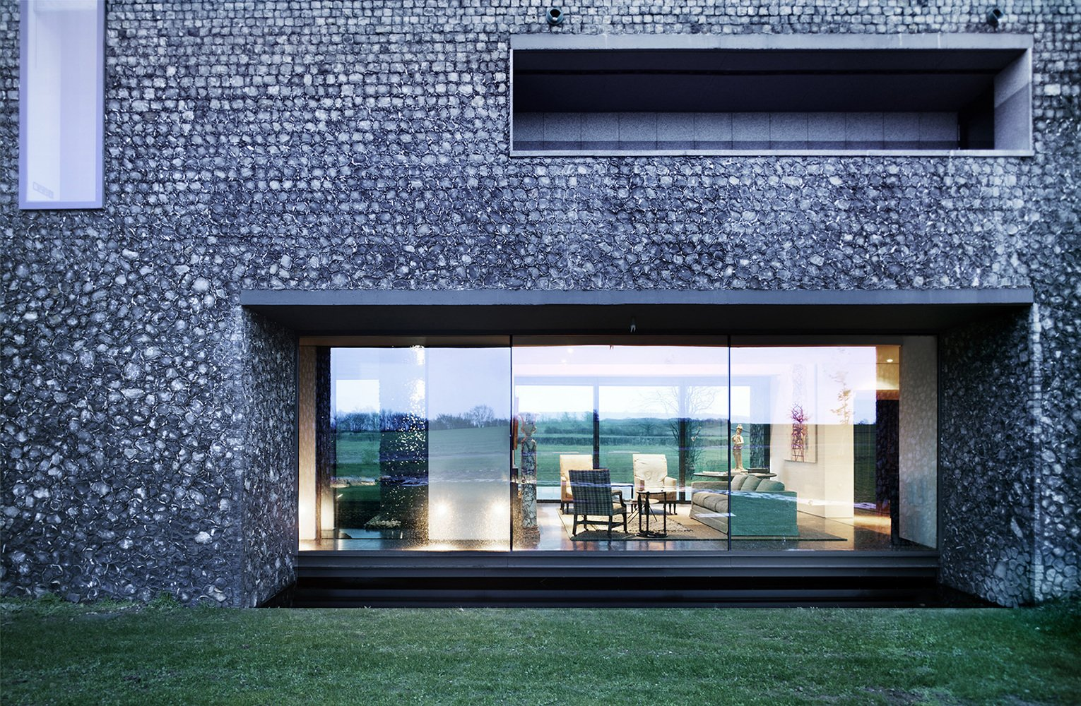 Windows A dark, almost black mortar on the lower portion of the home makes it feel grounded in the landscape.  Photo 11 of 16 in These 4 Modern Homes Around the World Take Advantage of Local Stone