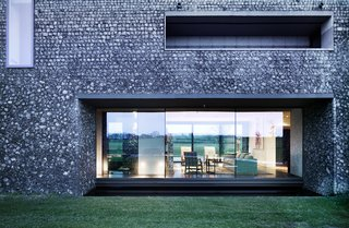 A dark, almost black mortar on the lower portion of the home makes it feel grounded in the landscape.