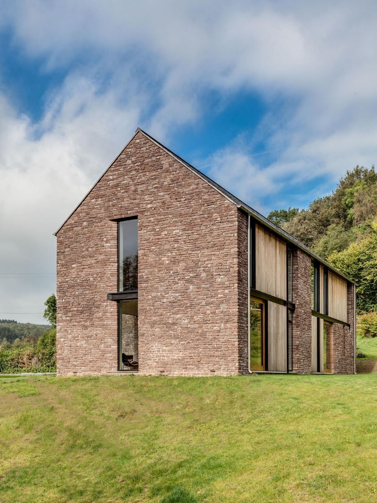 Exterior, House Building Type, Wood Siding Material, Stone Siding Material, and Shingles Roof Material The end gable of the house is covered in local sandstone.  Photo 15 of 16 in These 4 Modern Homes Around the World Take Advantage of Local Stone