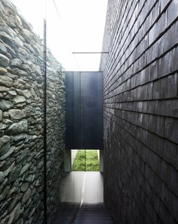 An open-air corridor is formed between the old stone walls and the new wooden shingles.