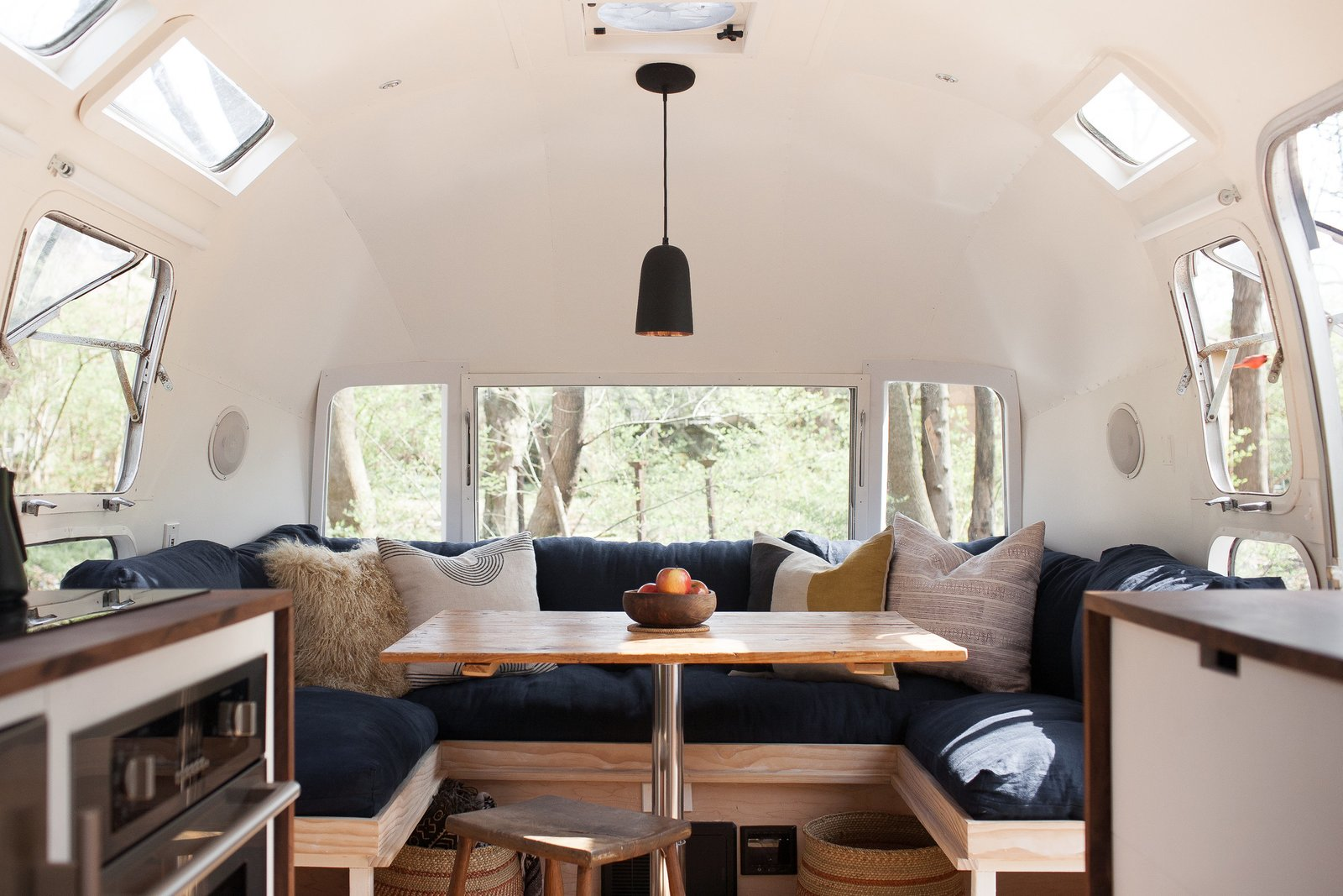 Ellen Prasse, an art teacher, and her partner, artist and writer Kate Oliver, transformed their lives and this 1977 Airstream over the course of a year, bringing the trailer back to life and giving it a classic but modern redo. Small touches, like a matte black faucet and light fixture paired with stainless steel appliances, along with a mixing of dark and light wood finishes prevent the space from feeling too matchy-matchy and overwhelming. Tagged: Dining Room, Bench, Pendant Lighting, Table, and Stools.  Best Photos from These 7 Vintage Airstreams Were Transformed Into Modern Escapes