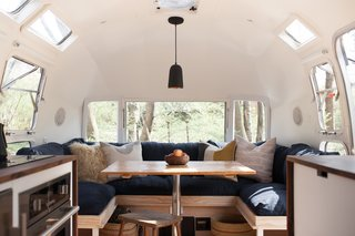 Ellen Prasse, an art teacher, and her partner, artist and writer Kate Oliver, transformed their lives and this 1977 Airstream over the course of a year, bringing the trailer back to life and giving it a classic but modern redo. Small touches, like a matte black faucet and light fixture paired with stainless steel appliances, along with a mixing of dark and light wood finishes prevent the space from feeling too matchy-matchy and overwhelming.