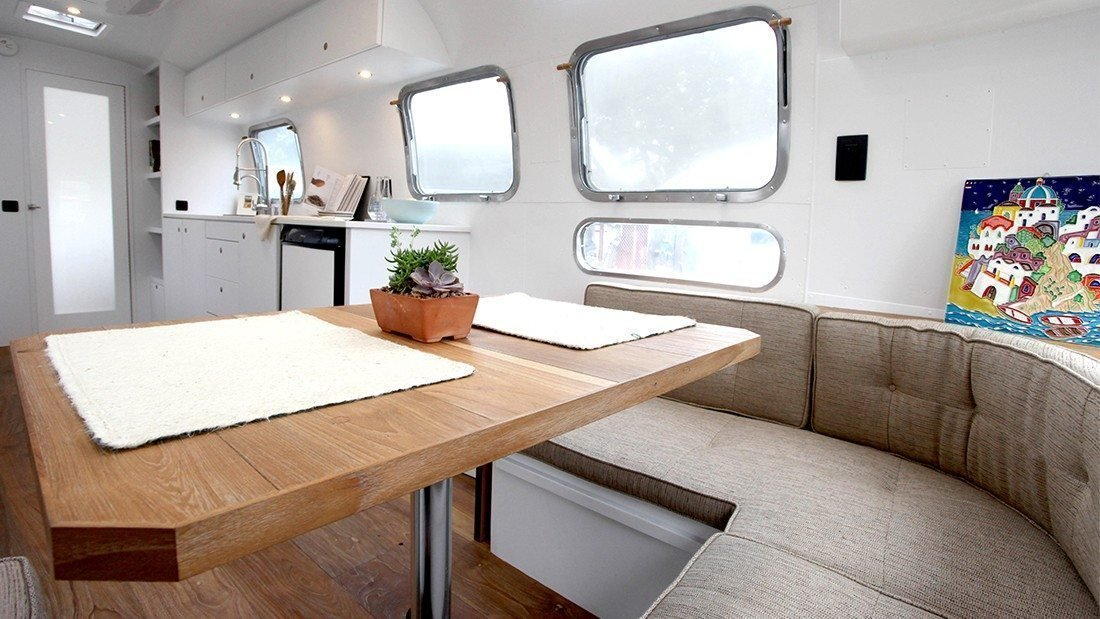 Dining Room, Table, Bench, Accent Lighting, Recessed Lighting, and Medium Hardwood Floor The late 1970s might be known for their bright colors and disco balls, but this 1978 Airstream remodeled by Hofman Architecture is the perfect picture of modern serenity. A combination of natural materials like raw wood and textured fabric with sleek white walls and cabinet make it feel spacious and calming. Wide-plank wood flooring gives it a rustic, warm touch, while custom-made cabinetry ensures that every inch is used.  Photo 1 of 8 in These 7 Vintage Airstreams Were Transformed Into Modern Escapes