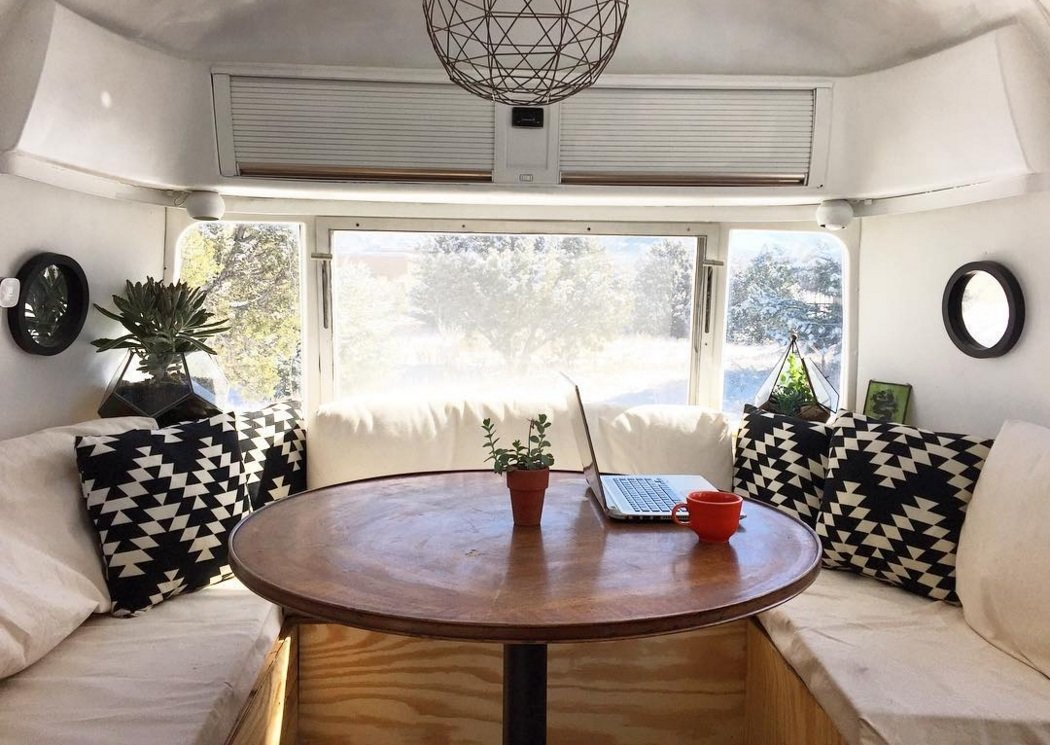 vintage airstream travel trailer dining area with overhead shelves