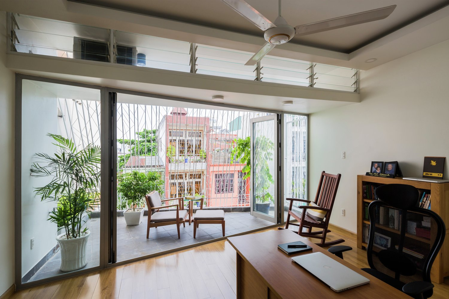 In this house in Thailand by Mel Schenck, a light shelf with translucent louvers above helps to regulate the bright light from an outside porch.  Photo 5 of 13 in 5 Architectural Tricks and Devices to Bring Natural Light Into Your Home