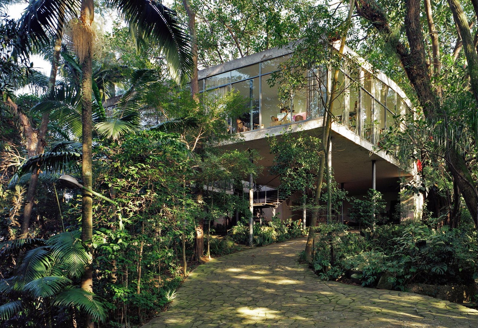 Outdoor and Trees Nestled in the jungle of São Paulo, Casa de Vidro (or Glass House) was the first built project by architect Lina Bo Bardi. Its glass volume stands on thin support columns that allow greenery to grow into the home.  Dwell's Favorite Outdoor Photos from Transformers of the Modern House: Albert Frey and Lina Bo Bardi at the Palm Springs Art Museum