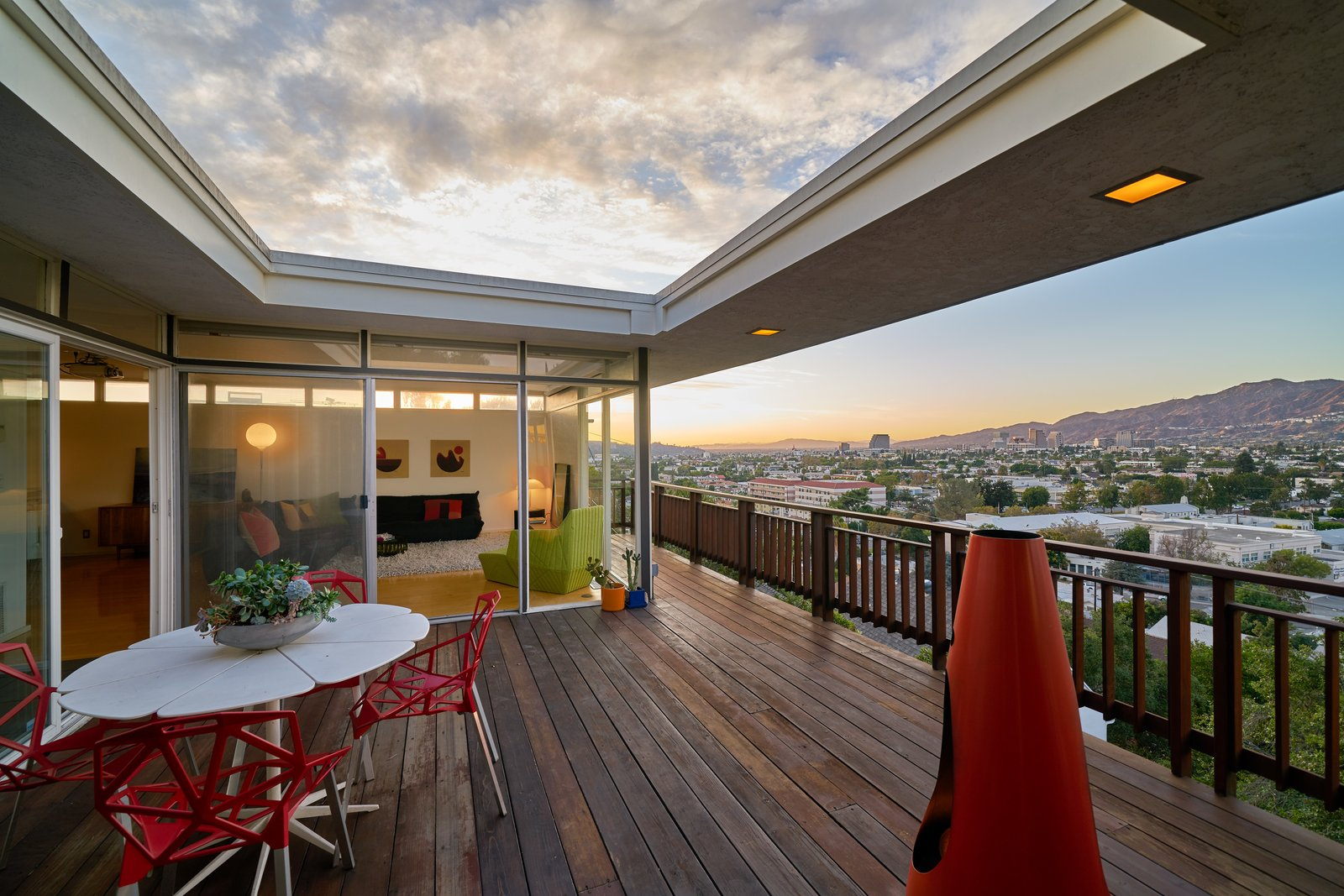 Outdoor, Large Patio, Porch, Deck, Wood Patio, Porch, Deck, and Wood Fences, Wall The outdoor terrance extends along the living room, allowing panoramic views of the city.  Photo 9 of 14 in A Midcentury-Modern Home in L.A. Designed by Richard Banta Is For Sale For $899K