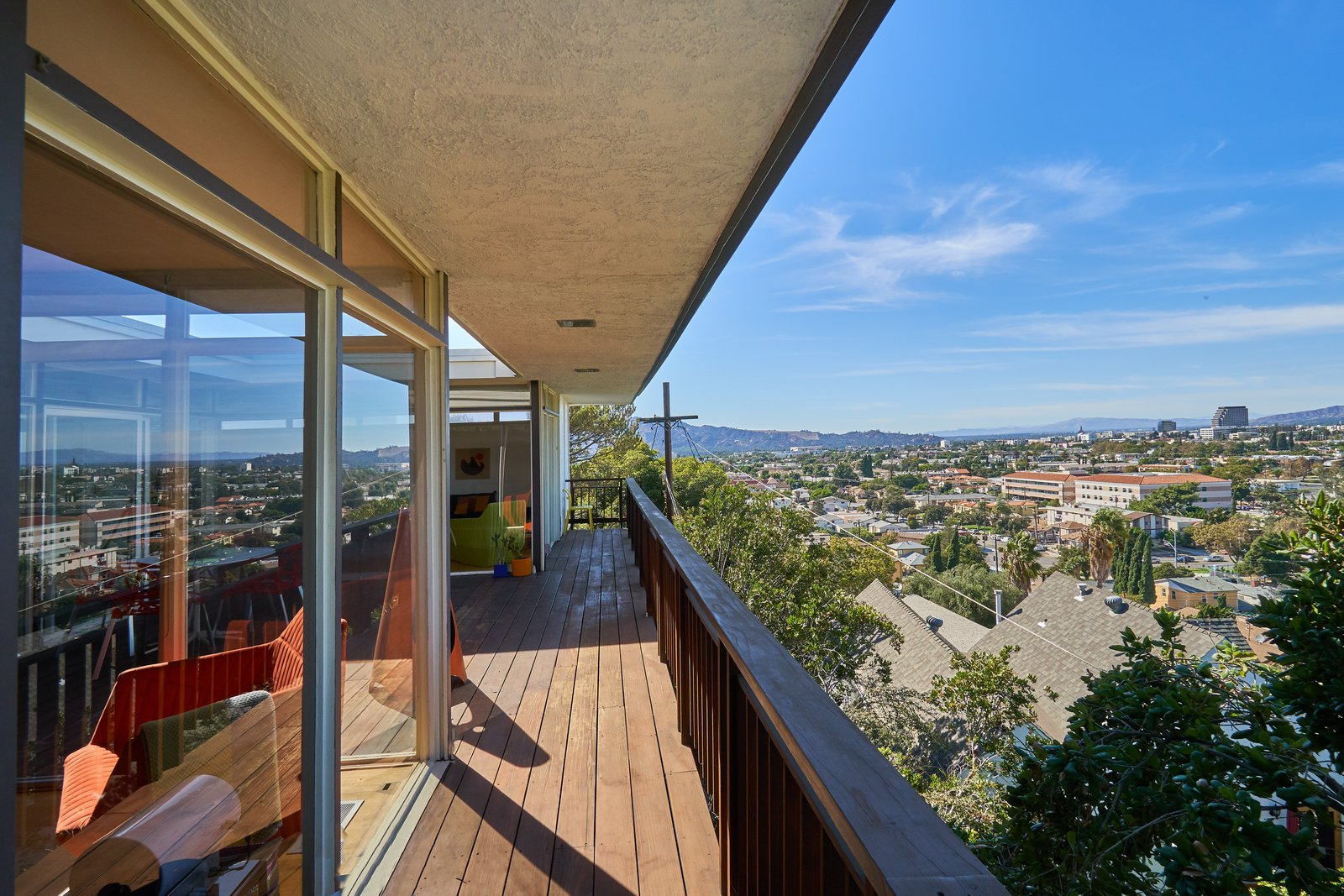 Outdoor and Wood Patio, Porch, Deck The rear of the house opens out to the rest of the city, while the facade facing the street is more closed off.  Photo 11 of 14 in A Midcentury-Modern Home in L.A. Designed by Richard Banta Is For Sale For $899K