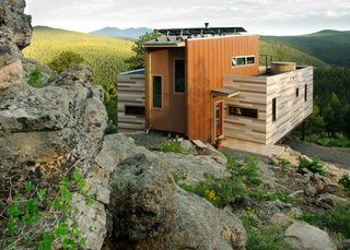 Within the 1500 square feet of this residence, the Denver, Colorado-based architecture firm Tomecek Studio implemented environmentally sensitive strategies including recycled materials, green roofs and photovoltaics. The residence is anchored by an existing rock outcropping and takes full advantage of the distant ridge views to the south. The main floor includes two shipping containers that saddlebag a wedge shaped space. The containers hold the function of bedrooms, bath, office, laundry and kitchen while the center space is used for entry, dining, and living. The upper floor is an open loft with a platform bed that slides on tracks outdoors as a reference to the quintessential camping experience.