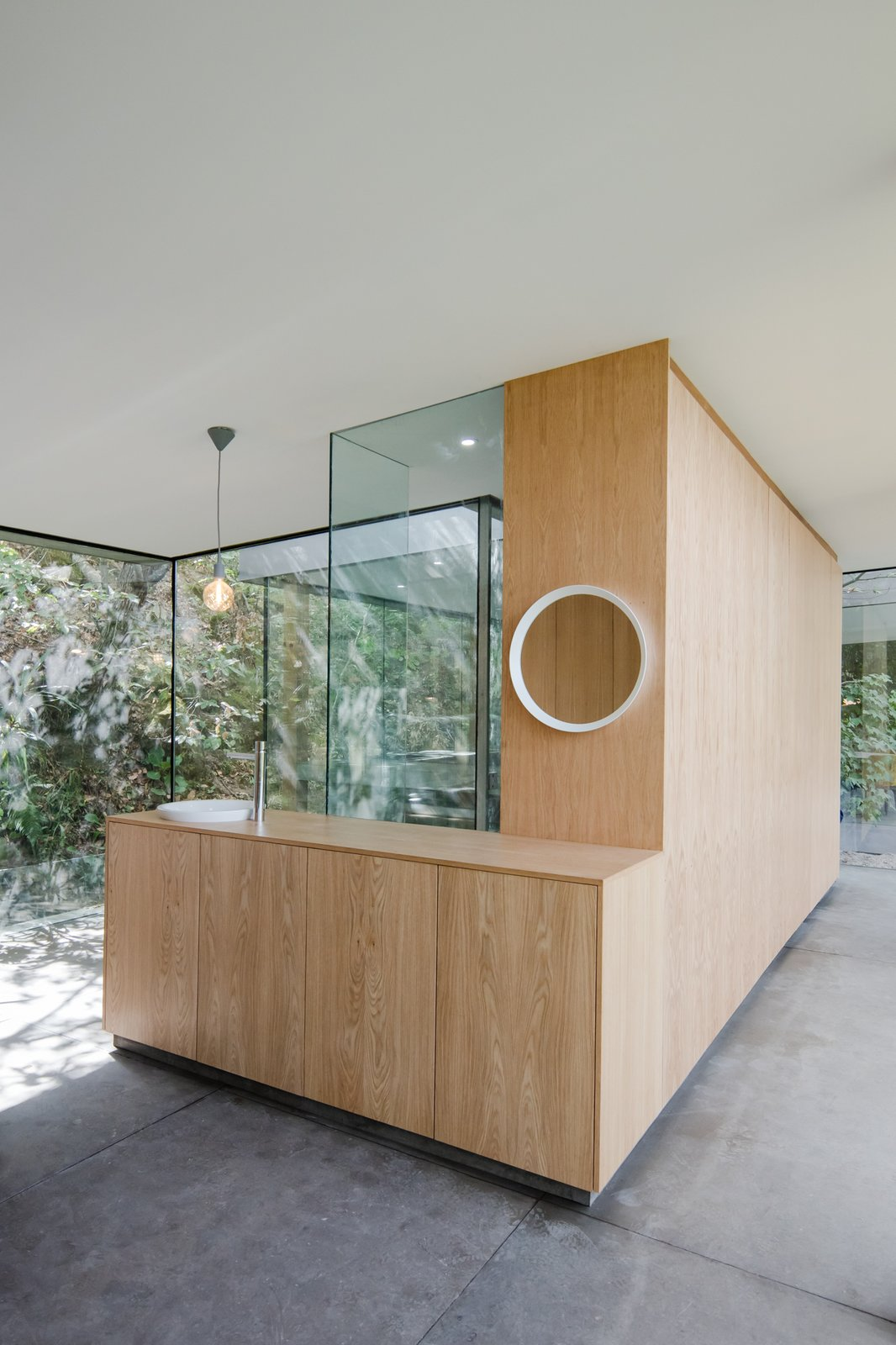 Living, Concrete, Pendant, and Bar Bookmatched wood veneer cabinetry brings a warm, tactile feel to the interiors.  Best Living Concrete Bar Photos from A Portuguese Glass House Uses Surrounding Foliage as a Privacy Screen