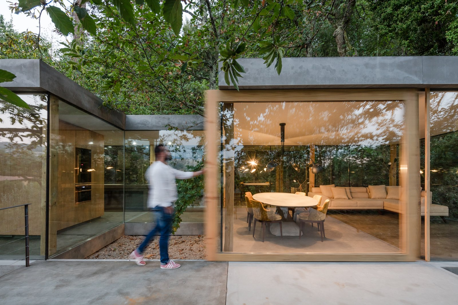 Doors, Wood, Exterior, and Sliding Door Type The home has sliding doors with thick wood frames.  Photo 11 of 15 in A Portuguese Glass House Uses Surrounding Foliage as a Privacy Screen