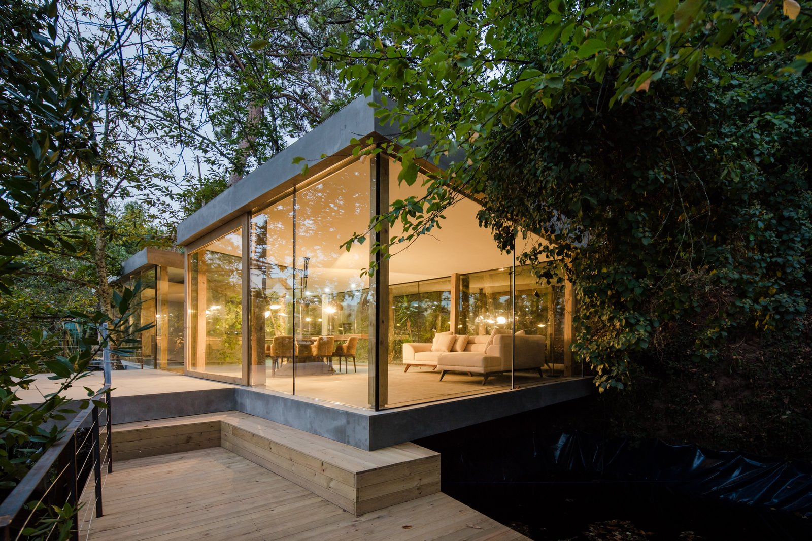 Outdoor, Trees, Wood Patio, Porch, Deck, Large Patio, Porch, Deck, Slope, and Concrete Patio, Porch, Deck Concrete floors and roof contrast with large expanses of glazing.  Photo 4 of 15 in A Portuguese Glass House Uses Surrounding Foliage as a Privacy Screen