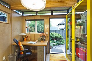 The interior of the she shed by Modern Shed features wood paneling and exposed beams. The prefabricated shed meant that it was ready to be used within a few days of its arrival on site.