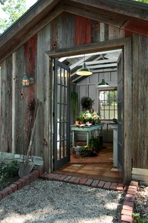 Inspired by a French farmhouse, this rustic she shed features multi-pane French doors, exposed roof rafters and joists, and earthy terra cotta floor tiles. With its wide-plank wood cladding sitting on gray stone foundations, this shed looks as though it has been around for centuries, but also has a simple, modern sensibility.