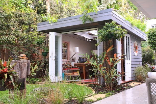 Shed & Studio, Living Space Room Type, and Living Room Room Type In Avalon, Australia, Olaf von Sperl and Cindy Goode Milman designed a she shed for the corner of Milman's backyard with $15,500. As an artist, she sought a space that would work as both a functional studio as well as a place of respite to enjoy the beautiful year-round weather of the area. With a roof of translucent polycarbonate panels topped with a planted green roof, this she shed is one-of-a-kind.