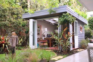 In Avalon, Australia, Olaf von Sperl and Cindy Goode Milman designed a she shed for the corner of Milman's backyard with $15,500. As an artist, she sought a space that would work as both a functional studio as well as a place of respite to enjoy the beautiful year-round weather of the area. With a roof of translucent polycarbonate panels topped with a planted green roof, this she shed is one-of-a-kind.