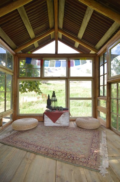Out in rural Oregon, a she shed was constructed almost entirely of old multi-pane windows that the owner was able to reuse from local construction projects. Since cross-ventilation was a priority, more than two-thirds of the windows can be opened. The wide-plank wood floors help continue to bring the outdoors in, and minimal interior furniture and finishes keep this space comfortable for meditation.