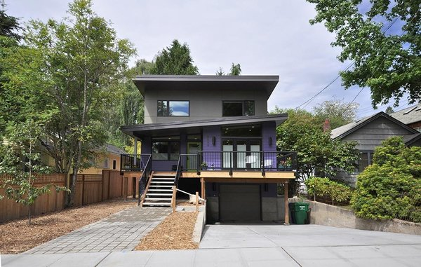 Inspired by the traditional shingle-clad homes in the neighborhood, this prefab home in Seattle was based off a base design by Method Homes and then customized by Grouparchitect to accommodate the client's needs and a unique site. Doors were widened, a rear porch was enclosed for an additional bedroom, and specialized storage including an enlarged laundry room, a generous pantry, and built-in cubbies for each member of the family were added.