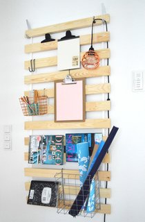 Typically hidden under a mattress to support it in a bedframe, the Ikea slatted Sultan Lade is instead an item for display in this hack.  The Sultan Lade is hung from the wall off two sturdy wall hooks, and then the slats hold a variety of items, from lamps and books to Ikea S-hooks supporting storage baskets.