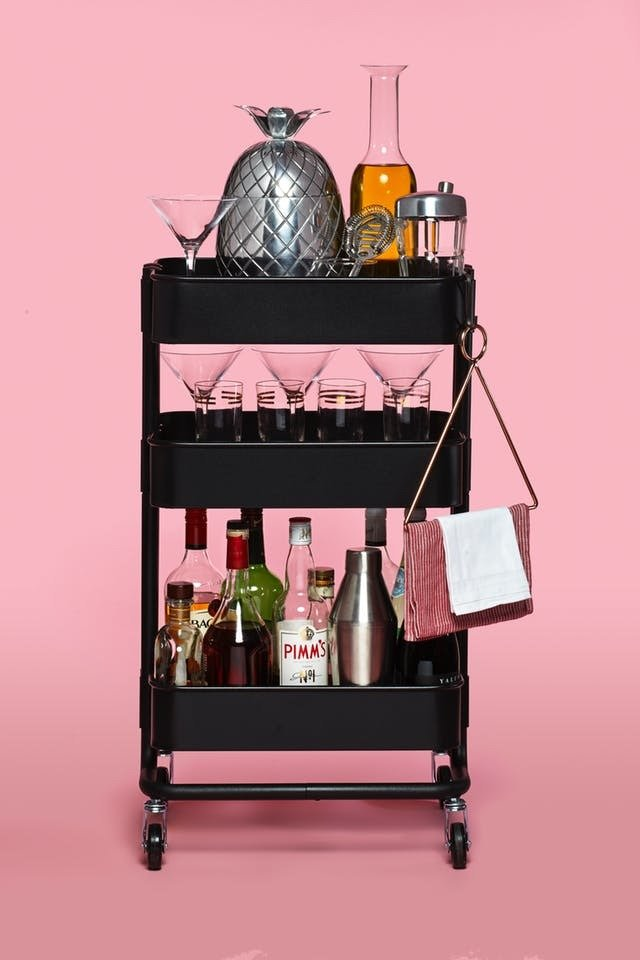 Ikea's utility cart, the Raskog cart, makes for a refined and easily movable bar cart -- it already comes with wheels, and just needs some stemware, a wine rack, and other accoutrements, and voila! There you have one of the easiest Ikea hacks out there.