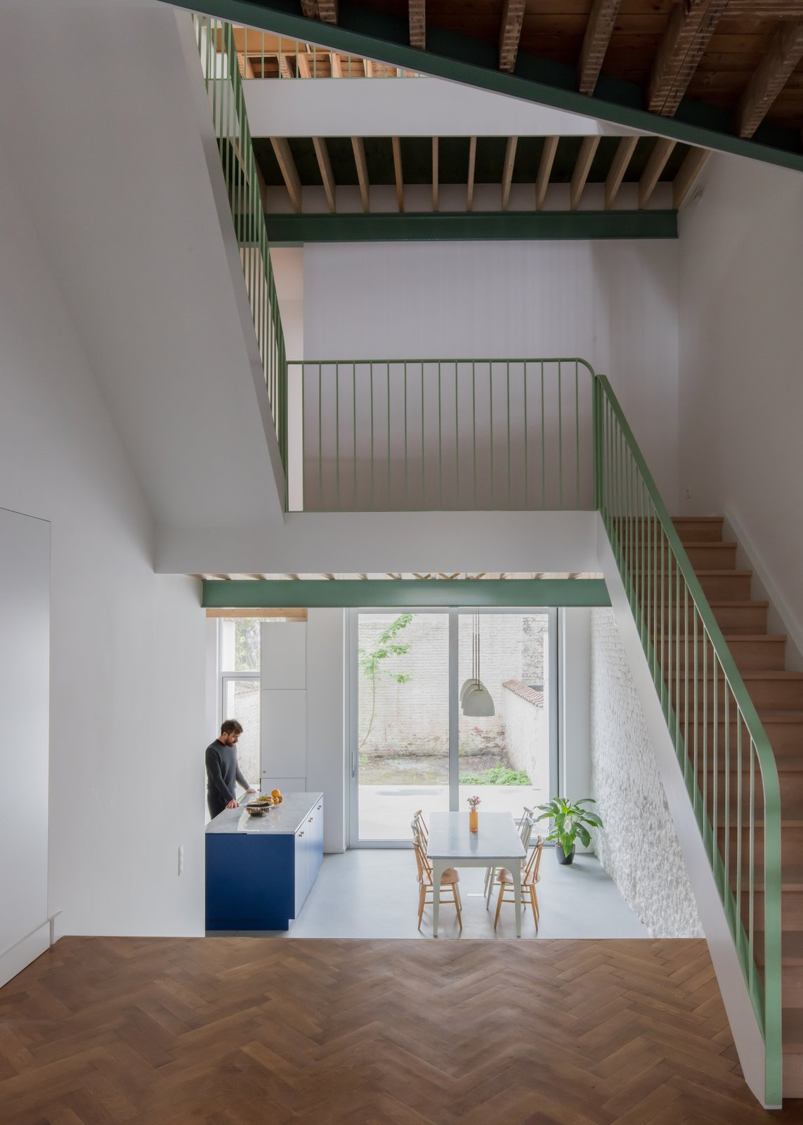 Staircase, Wood Tread, and Metal Railing Located in the center of the home, the simple, yet striking staircase connects three floors.    Photo 1 of 13 in A Mint-Green Staircase Adds Radiant Color to This Restored Townhouse