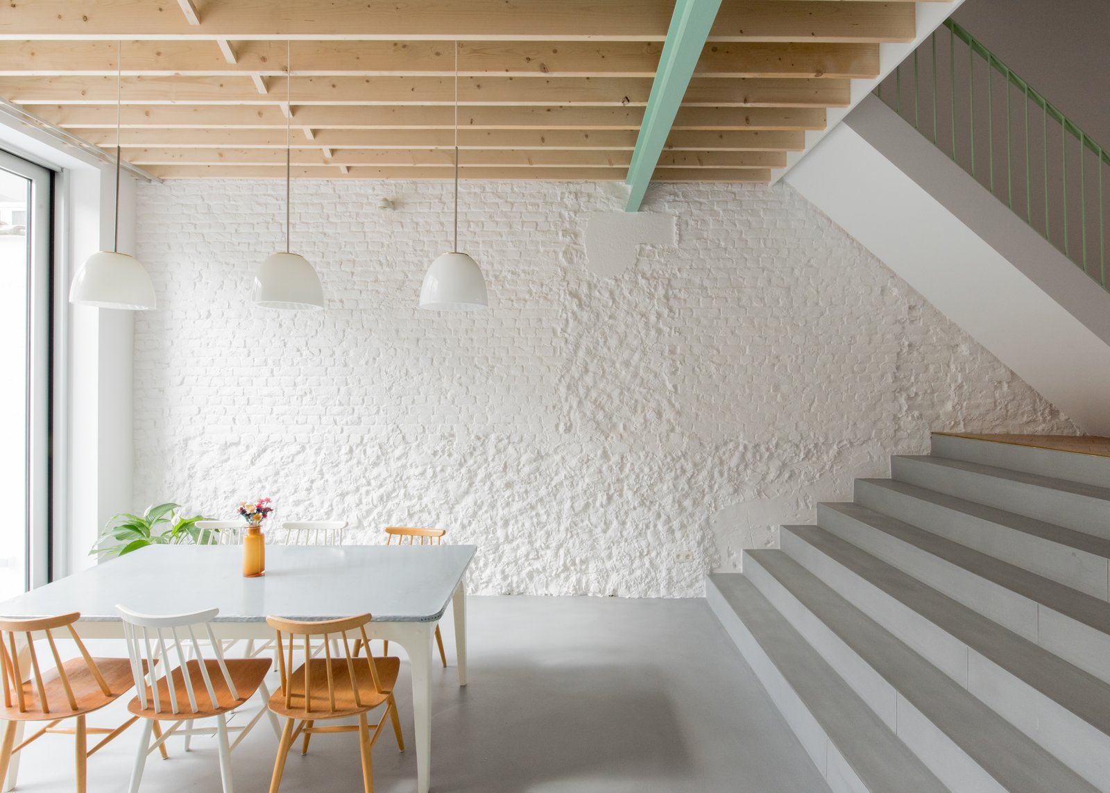 Dining Room, Pendant Lighting, Concrete Floor, Chair, and Table On the ground level, the kitchen is reached by stepping down toward the back of the home, ultimately leading out to a rear yard.    Best Photos from A Mint-Green Staircase Adds Radiant Color to This Restored Townhouse