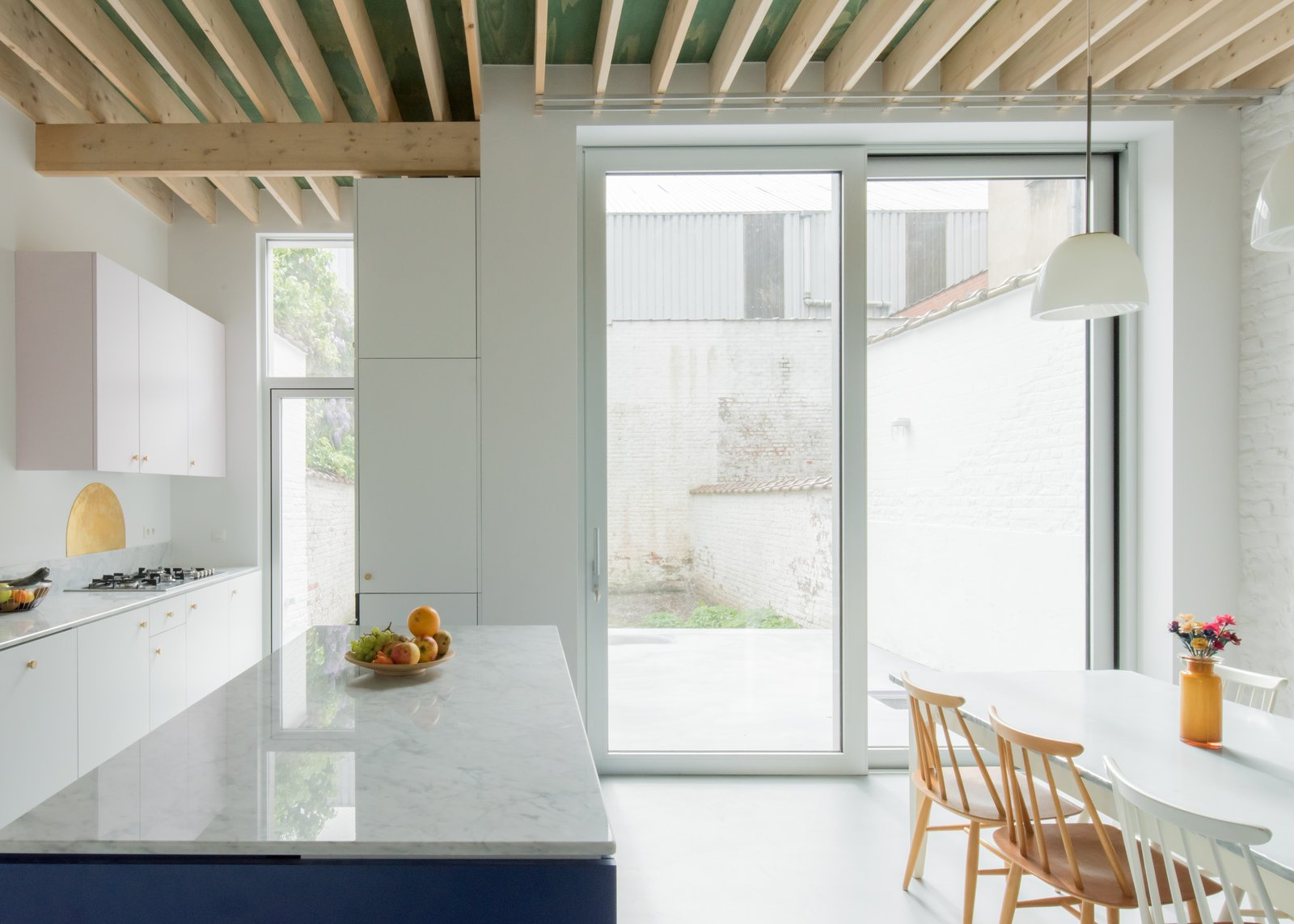Kitchen, Pendant, Concrete, Colorful, Cooktops, and White Floor-to-ceiling windows allow light to penetrate into the kitchen and the central hallway.    Best Kitchen Concrete Colorful White Photos from A Mint-Green Staircase Adds Radiant Color to This Restored Townhouse