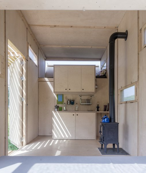 Because the tiny house can be used off-grid, the inside is heated with a wood-burning stove, which is a stark graphic variation to the rest of the wood interiors.