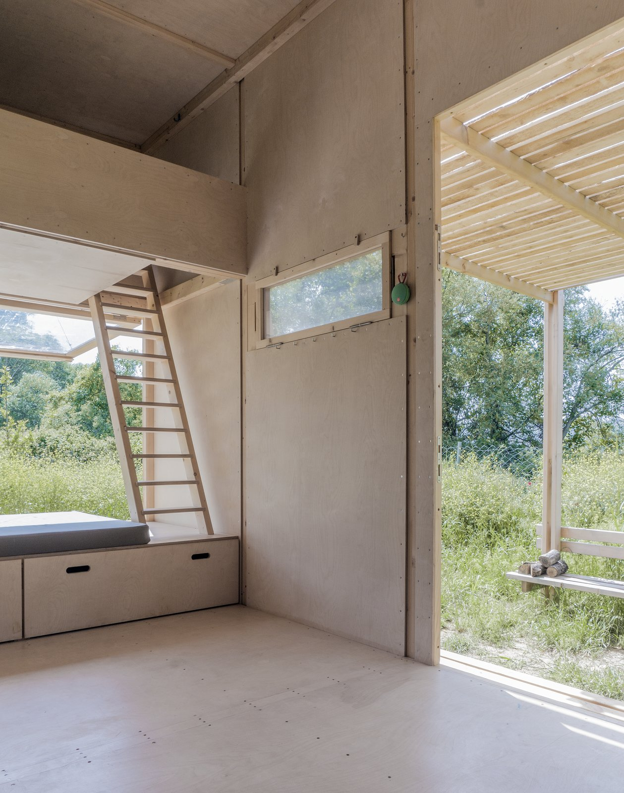 Living Room, Plywood Floor, and Bench Beds are lofted above the kitchenette and large bench, and are accessible by wooden ladders.    Best Photos from This Off-Grid Turkish Cabin Features a Nifty Pulley System