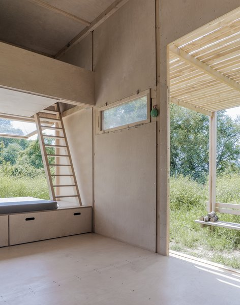 Living, Plywood, and Bench Beds are lofted above the kitchenette and large bench, and are accessible by wooden ladders.    Best Living Photos from This Off-Grid Turkish Cabin Features a Nifty Pulley System