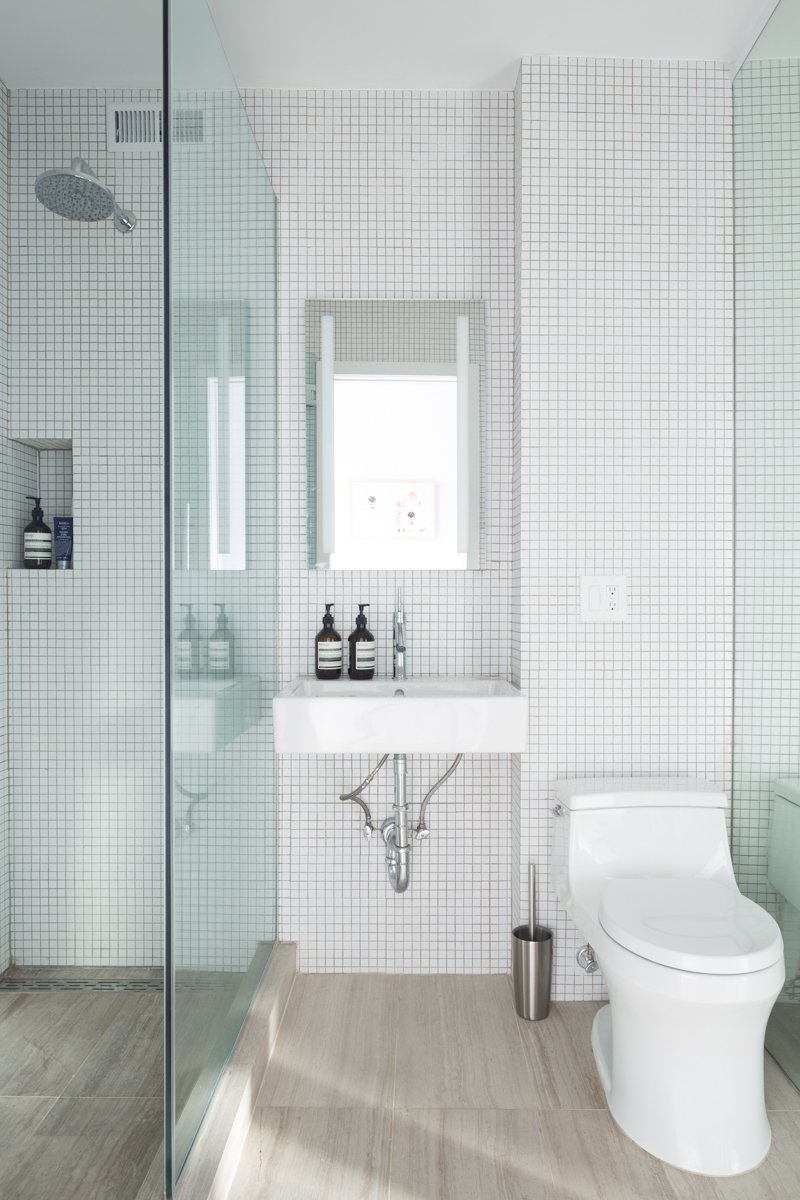 Bath, One Piece, Wall Mount, Porcelain Tile, Open, and Mosaic Tile The bathroom has classic square tiles on the walls, rising up to the ceiling for a modern touch.    Bath Mosaic Tile One Piece Open Photos from Vivid Accent Colors Turn This Tiny Abode Into a Dreamy Oasis