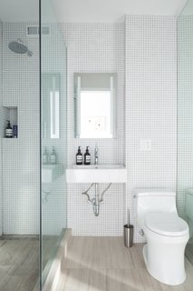 The bathroom has classic square tiles on the walls, rising up to the ceiling for a modern touch.