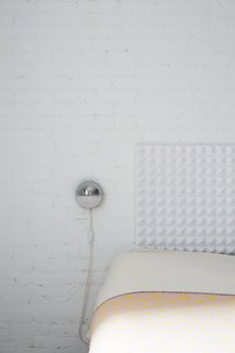 The headboard and brick wall provide much-needed texture and depth in the bedroom.