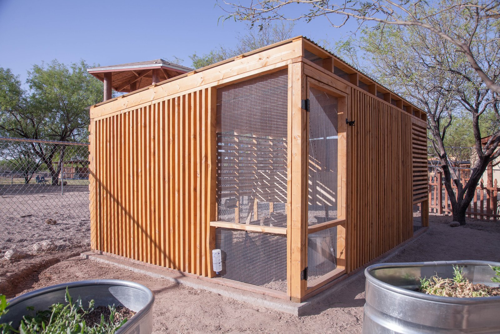 Exterior, Shed, Metal, Flat, and Wood Each facade of the coop is distinct based on orientation to the sun.  Exterior Shed Wood Photos from Budget Breakdown: An Architect Builds a New Chicken Coop For Less Than $1.5K