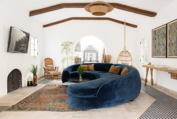 Curved walls were the source of inspiration for the custom, undulating, 22-foot-long sofa, clad in blue velvet, which acts as a plush focal point in the space. Its blue tone contrasts with the crisp, white walls in a modern take on the typical blue and white color palette of the Greek isles.