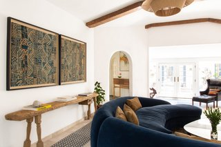 The curvature of the blue sofa is reminiscent of the arched openings leading into the space.