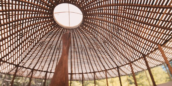 The woven wood ceiling of the gallery houses Bello's wooden sculptures but is a piece of artwork in and of itself.
