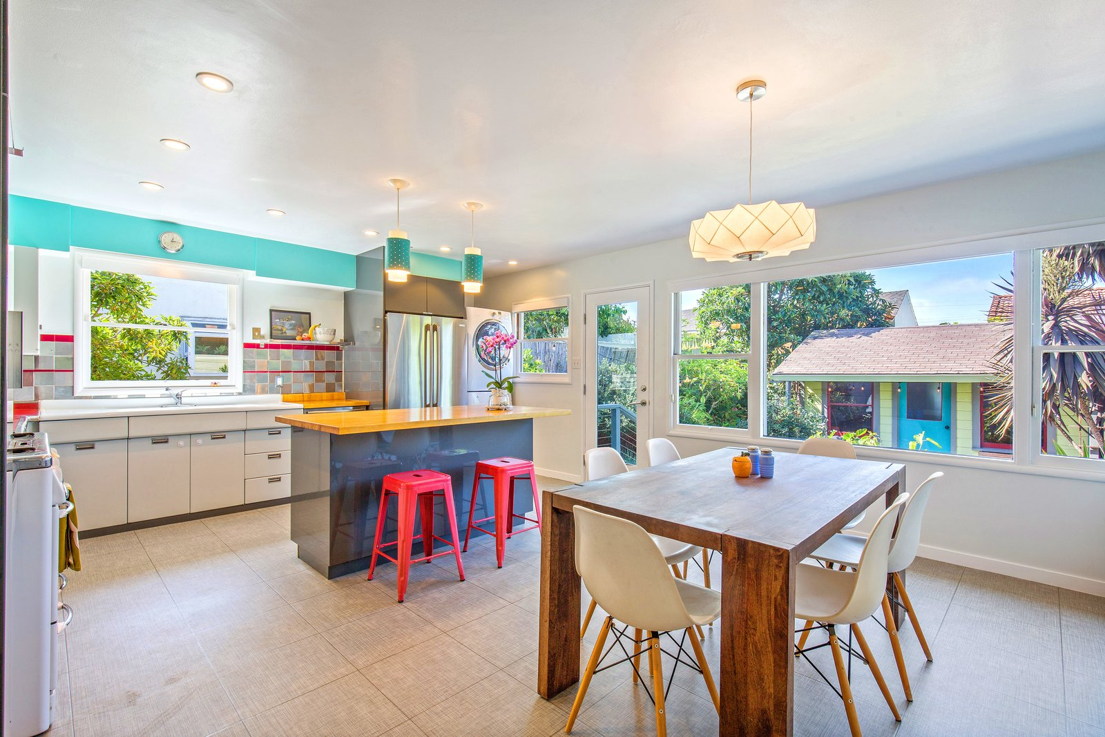 Kitchen, Refrigerator, Ceramic Tile Backsplashe, and Pendant Lighting The kitchen retains its original 1950s cabinetry, oven, and tiles, but has been supplemented with modern appliances and an island, among other features.  Best Photos from A Midcentury Charmer in the Bay Area Is Listed at $749K